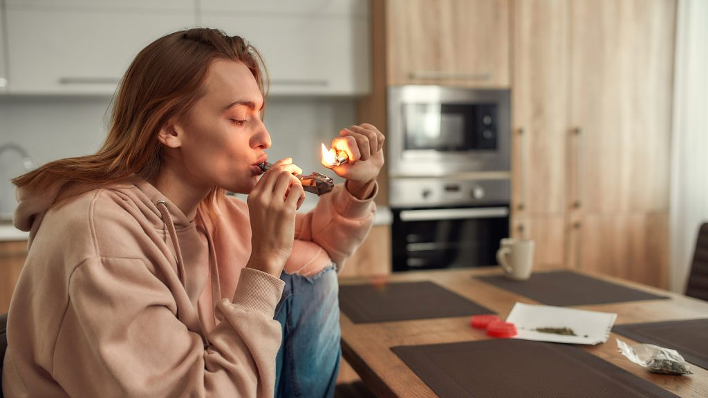 Young caucasian woman lighting cannabis in the bowl of metal pipe while sitting in the kitchen. Buds in a plastic bag and red marijuana grinder on the table. Weed legalization concept. Side view